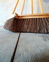 grands balais sur les travaux ménagers de plancher en bois photo