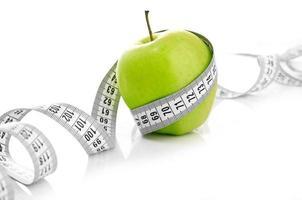 mètre ruban enroulé autour d'une pomme verte photo