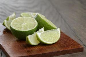 limes tranchées sur planche de bois photo