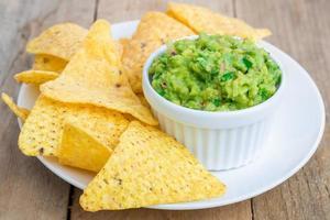 tasse de guacamole en morceaux servi avec des nachos