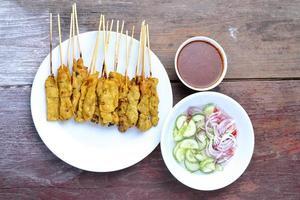 Satay de porc avec sauce aux arachides, fond de table en bois.