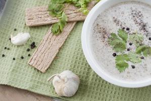 soupe à la crème de champignons servie avec de l'ail et des légumes verts photo