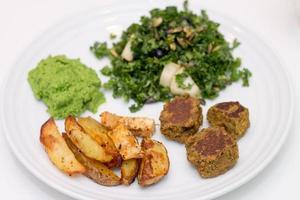 pommes de terre au four, falafels, mousse de pois et salade sur plaque blanche