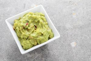 trempette de guacamole dans un plat blanc photo