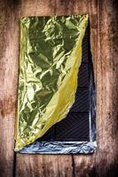 Tablette de chocolat noir tourné sur fond de bois, gros plan. photo