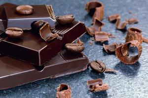 chocolat noir et grains de café sur une table en pierre
