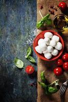tomates cerises, feuilles de basilic, fromage mozzarella et huile d'olive f photo