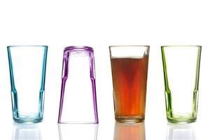 quatre verres à boire colorés, un avec du cola photo