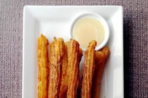 churros de beignets espagnols faits maison avec sauce au chocolat blanc photo