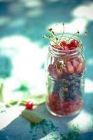 cerises et groseilles dans un pot sur table bleue photo