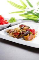 Salade thaïlandaise chaude sur une plaque blanche sur fond noir photo