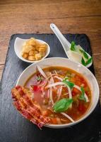 soupe de légumes servie avec bacon croustillant, fromage et croquettes photo