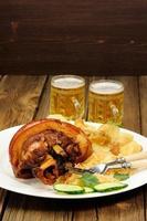 eisbein avec de la bière légère sur fond en bois photo