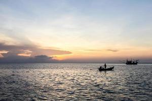 bateau à longue queue et coucher de soleil en mer, koh phangan, surat thani photo