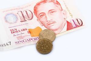 Billets et pièces en dollars singapouriens sur fond blanc,