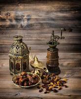 lanterne orientale et moulin. raisins secs et dattes sur fond de bois photo