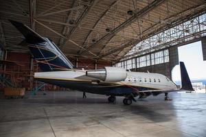 avion d'affaires reste dans le hangar. photo