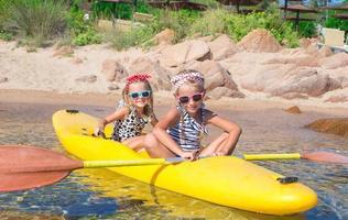 petites filles adorables appréciant le kayak sur kayak jaune photo