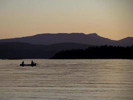 kayakistes au coucher du soleil avec un ciel violet. photo