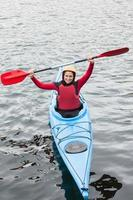 femme heureuse dans un kayak acclamant la caméra photo