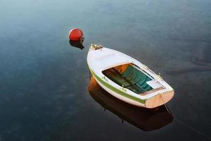 bateau à rames à la bouée dans le port photo