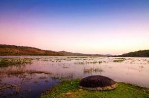 paysage du soir au bord d'un lac avec un coracle photo