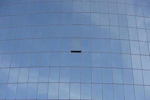 Fenêtre entrouverte sur un gratte-ciel en verre