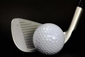 balle de golf et club closeup sur fond noir photo