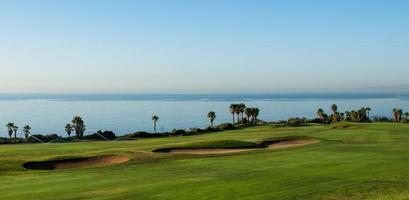 parcours de golf au bord de la mer au coucher du soleil photo