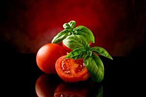 tranches de tomates au basilic sur table en verre photo