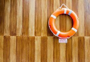 la bouée de sauvetage orange sur fond de mur en bois photo