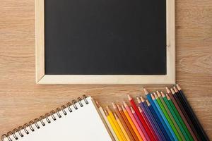 crayons de couleur avec carnet et tableau noir photo