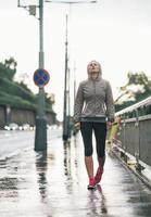 portrait, de, fitness, jeune femme, marche, dans, ville pluvieuse photo