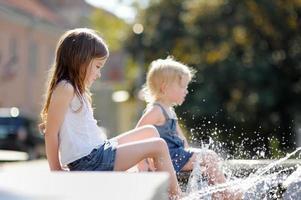petites sœurs s'amusant dans une fontaine photo