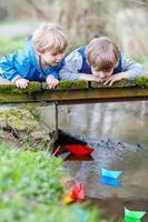 deux petits frères jouant avec des bateaux en papier au bord d'une rivière photo