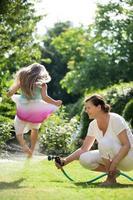 Grand-mère arrosant le jardin, fille sautant par-dessus le jet d'eau photo