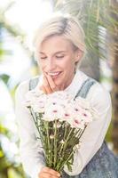 jolie blonde femme tenant un bouquet de fleurs photo