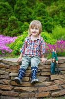 jeune jardinier posant sur le parterre de fleurs photo