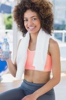 fit jeune femme tenant une bouteille d'eau au gymnase