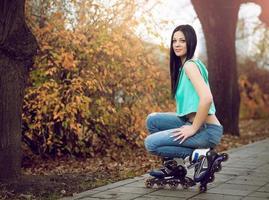 jeune fille à genoux sur des patins à roulettes.