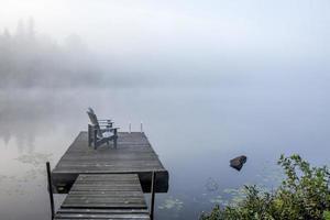 chaises sur un quai donnant sur un lac brumeux
