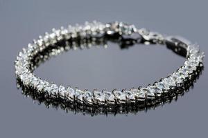 bracelet en argent avec diamants sur fond gris photo