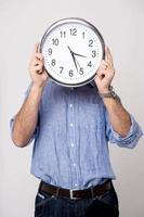 homme tenant une horloge, montre l'heure. photo
