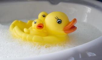 famille de canards en caoutchouc dans le bain avec bain moussant photo