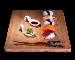 cinq espèces de sushi de poisson sur planche de bambou