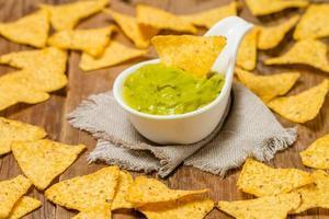 nachos mexicains avec sauce guacamole à la main