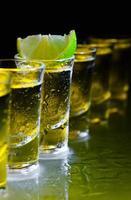 tequila et citron vert sur table en verre