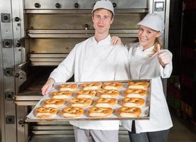 Boulangers avec plaque de cuisson en boulangerie montrant les pouces vers le haut photo