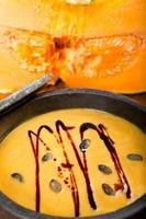 soupe de citrouille dans une poêle en pierre ollaire, avec de la citrouille en arrière-plan, photo