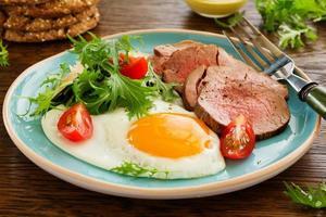 œufs brouillés avec rôti de boeuf et salade.